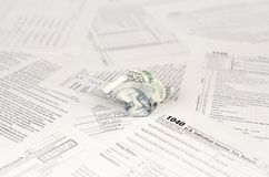 1040 Individual income tax return form and crumpled hundred dollar bill. Loss of money to pay taxes concept royalty free stock photos
