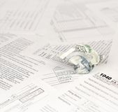 1040 Individual income tax return form and crumpled hundred dollar bill. Loss of money to pay taxes concept royalty free stock image