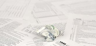 1040 Individual income tax return form and crumpled hundred dollar bill. Loss of money to pay taxes concept royalty free stock photo