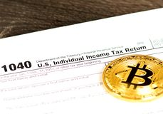 Individual income tax return 1040 form with metallic bitcoin coin royalty free stock photo