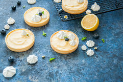 Individual lemon curd tarts with blueberry jam. Meringue and basil leaves on a blue stone background. Flat lay and copy space Stock Photos