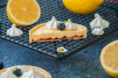 Individual lemon curd tarts with blueberry jam. Meringue and basil leaves on a blue stone background. Flat lay and copy space Stock Photography
