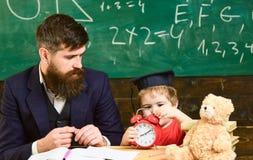 Individual lesson concept. Boy, child on calm face holds alarm clock while teacher talk to kid. Teacher with beard