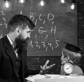 Individual lesson concept. Teacher with beard, father teaches little son in classroom, chalkboard on background. Boy royalty free stock images