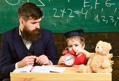 Individual lesson concept. Teacher with beard, father teaches little son in classroom, chalkboard on background. Boy Stock Image