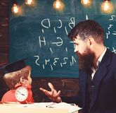 Individual lesson concept. Teacher with beard, father teaches little son in classroom, chalkboard on background. Boy stock photos