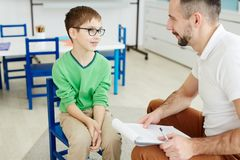 Individual lesson. Cute schoolboy in eyeglasses answering questions of teacher at individual lesson royalty free stock photography