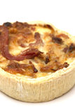 Individual quiche. An individual mini quiche on a white board stock photos