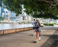 Person riding an electric scooter on a footpath. stock images