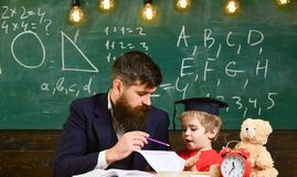Individual schooling concept. Kid studies individually with teacher, at home. Father with beard, teacher teaches son. Little boy. Teacher and pupil in royalty free stock image
