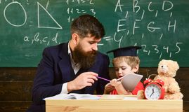 Individual schooling concept. Teacher and pupil in mortarboard, chalkboard on background. Kid studies individually with. Teacher, at home. Father with beard stock images