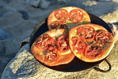 Individual baked tomato foccacia bread. Individual serving size baked focaccia bread on rocky seashore in Baja Mexico Stock Photo