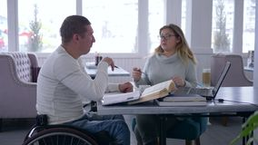 Individual training for disabled, smart teacher female into glasses provides teaching for invalid man on wheelchair stock video