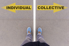 Individual vs Collective text arrows on asphalt ground, feet and Royalty Free Stock Images