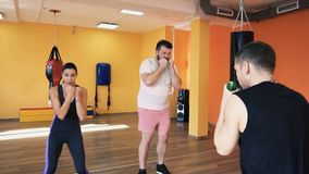 A slim girl and an overweight man train blows. Private coach with dumbbells. Individual weight loss drills for thick guy stock video footage