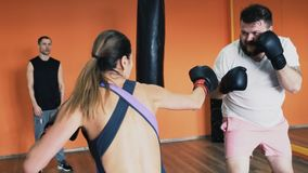 Fat guy and slender girl fight in boxing gloves. Individual weight loss drills for thick male. Training with personal stock footage