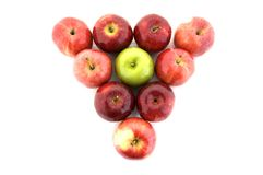 Individuality. A green apple in a triangle of red apples Stock Image