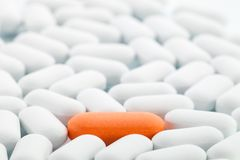Individuality - Orange pill between white ones Royalty Free Stock Images