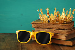 Individuality and unique concept. Old medieval gold crown and cool sunglasses. On wooden table Royalty Free Stock Images