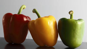 Individuality and uniqueness. Coloured bell peppers, red, green and yellow. Uniqueness and individuality conceptual image Royalty Free Stock Images