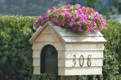 Blooming Mail Box. Individually styled US mail box house with bloomin pink flowers Stock Photo