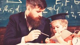Individueel het scholen concept De vader met baard, leraar onderwijst zoon, weinig jongen Jong geitjestudies individueel met lera royalty-vrije stock afbeelding