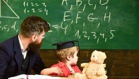 Individueel lessenconcept De jongen, kind in gediplomeerd GLB bekijkt gekrabbel op bord terwijl de leraar verklaart leraar royalty-vrije stock afbeeldingen
