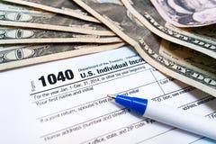 1040 individuele belastingaangiftevorm met pen en dollargeld bils dichte omhooggaand Royalty-vrije Stock Foto