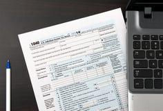 Individuell självdeklarationform 1040 för USA på en tabell med bärbara datorn och pennan Royaltyfria Foton