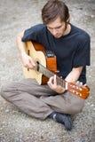 Individuo áspero del país que toca su guitarra Imágenes de archivo libres de regalías