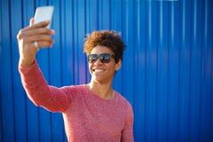 Individuo adolescente moderno que toma un autorretrato sobre fondo colorido Fotos de archivo