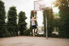 Individuo adolescente que juega el streetball Imagen de archivo libre de regalías