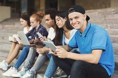 Individuo adolescente que usa la tableta digital y sonriendo en la cámara imágenes de archivo libres de regalías