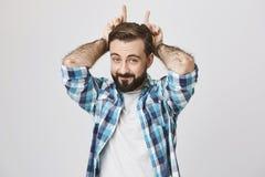 Individuo adulto europeo hermoso con la barba y bigote que muestra los cuernos con los dedos índices a mano, imitando el diablo o Fotos de archivo