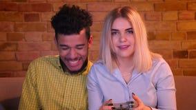 Individuo africano con su videojuego caucásico rubio del juego de la novia con la palanca de mando alegre en hogar acogedor almacen de video