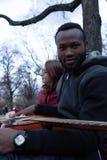 Individuo africano con una guitarra acústica y una muchacha blanca con los vidrios en el parque imagen de archivo libre de regalías