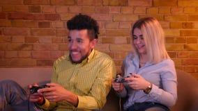 Individuo africano joven con su novia caucásica rubia que juega el videojuego con las palancas de mando en atmósfera casera acoge metrajes