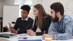 Individuo africano joven que explica algo a sus colegas Grupo diverso feliz de estudiantes o de funcionamiento joven del equipo d almacen de video