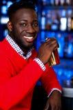 Individuo africano que bebe la cerveza enfriada imagen de archivo libre de regalías