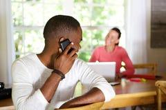 Individuo africano que hace una llamada de teléfono y que mira detrás la mujer Foto de archivo