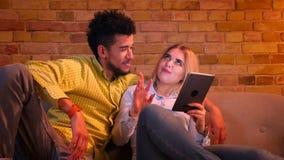 Individuo africano y muchacha caucásica que se sientan en el sofá con la tableta y que ríen alegre en casa almacen de video
