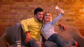 Individuo africano y muchacha caucásica que se sientan en el sofá que hace las selfie-fotos en el teléfono que es alegre y bastan almacen de video