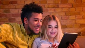 Individuo africano y muchacha caucásica que se sientan en el sofá que mira atento en la tableta en casa metrajes