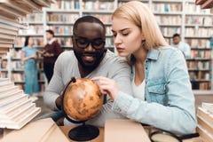 Individuo afroamericano étnico y muchacha blanca rodeados por los libros en biblioteca Los estudiantes están utilizando el globo fotografía de archivo