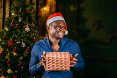Individuo afroamericano con la sonrisa encantadora que celebra el regalo de la Navidad en manos Fotos de archivo libres de regalías