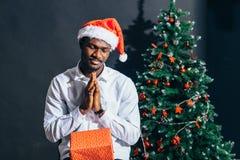 Individuo afroamericano con la sonrisa encantadora que celebra el regalo de la Navidad en manos Fotografía de archivo libre de regalías
