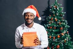 Individuo afroamericano con la sonrisa encantadora que celebra el regalo de la Navidad en manos Imagen de archivo libre de regalías