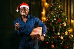 Individuo afroamericano con la sonrisa encantadora que celebra el regalo de la Navidad en manos Fotografía de archivo