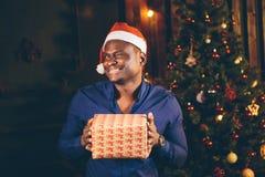 Individuo afroamericano con la sonrisa encantadora que celebra el regalo de la Navidad en manos Imágenes de archivo libres de regalías