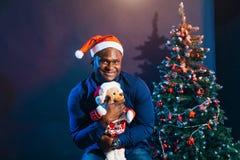 Individuo afroamericano con la sonrisa encantadora que celebra el regalo de la Navidad en manos Imagenes de archivo